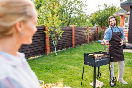 selective focus of couple having barbecue on backyard of country house on summer day
