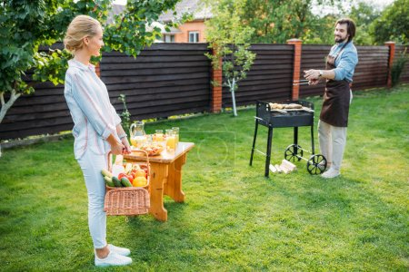 couple having barbecue on backyard on summer day
