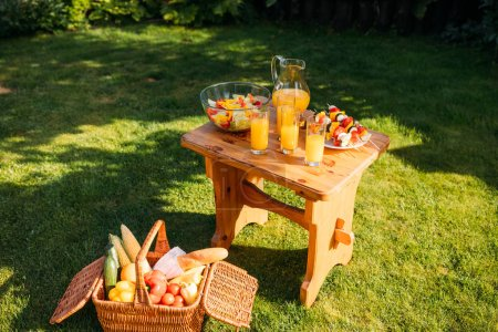 close up view of basket with food for picnic, glasses of  juice and fresh salad on wooden chair on green lawn
