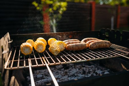 close up view of cooking process of corn and sausages on grill on summer day