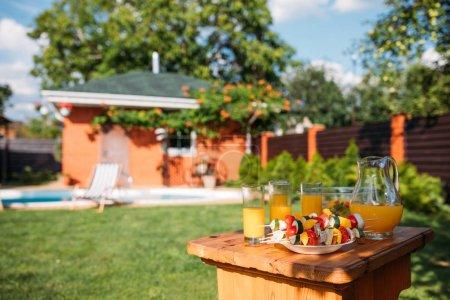 Foto de Enfoque selectivo de verduras frescas para la barbacoa y vasos de jugo en el patio trasero - Imagen libre de derechos