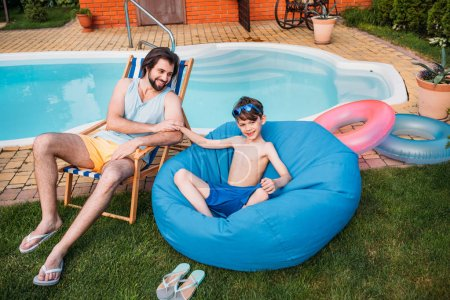 smiling father and son resting near swimming pool on backyard on summer day