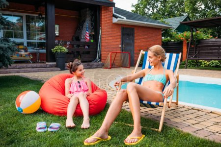 mother and smiling daughter resting near swimming pool on backyard on summer day