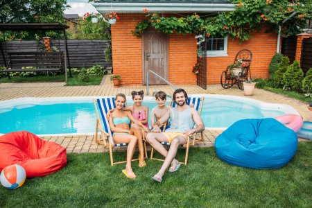 smiling family spending time near swimming pool at countryside backyard on summer day