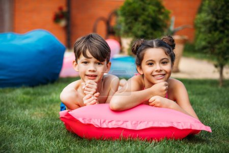 portrait of cute kids resting on inflatable mattress on green lawn on backyard of country house