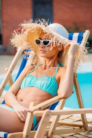 portrait of beautiful woman in straw hat and sunglasses resting on beach chair at swimming pool on summer day
