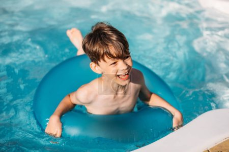 portrait of happy boy with inflatable ring swimming in swimming pool on summer day