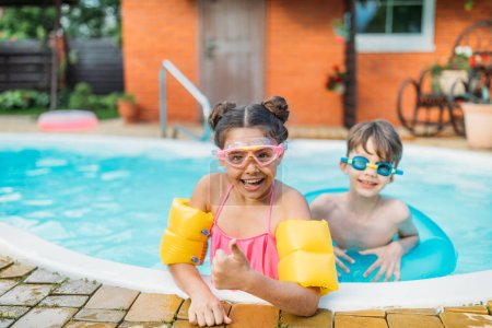 little siblings swimming in swimming pool together on summer day