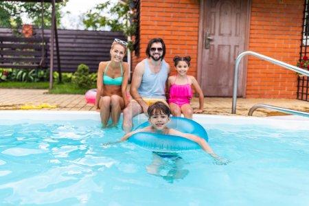 Photo pour Mise au point sélective de famille heureuse, passer du temps près de la piscine au jardin de campagne le jour de l'été - image libre de droit