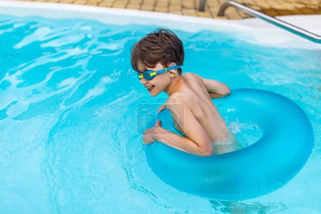 side view of happy boy in swimming glasses with inflatable ring swimming in swimming pool on summer day