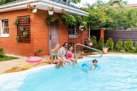 happy family spending time near swimming pool at countryside backyard on summer day