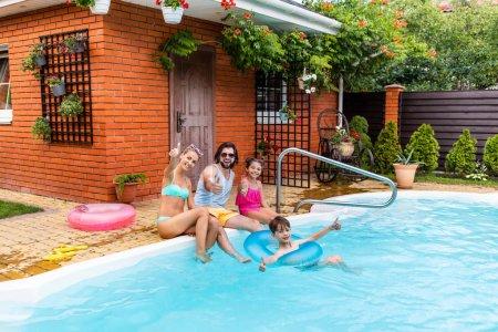 Photo pour Famille apparaît-il pouces tandis que les dépenses de temps près de piscine le jour de l'été - image libre de droit