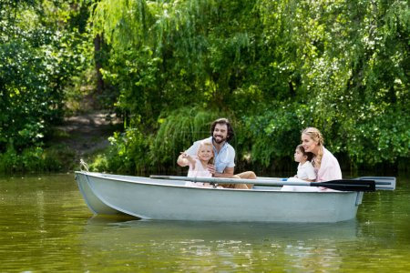 young family spending time together in boat on river at park and looking away