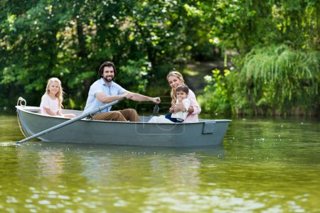 happy young family spending time together in boat on river at park and looking at camera