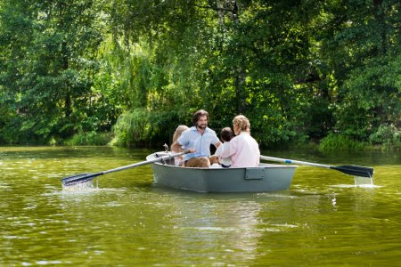 happy young family spending time together in boat on river at park
