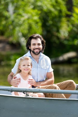 happy father and daughter sitting in boat on lake at park and looking at camera