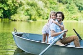 happy daughter embracing father from behind while they riding boat on lake at park