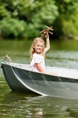 beautiful little child playing with toy plane floating in boat on lake