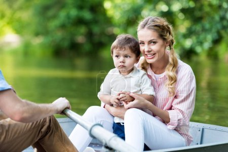 parents riding boat on lake with son at park
