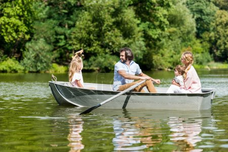 side view of beautiful young family riding boat on river at park on sunny day