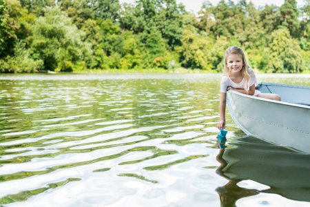 beautiful little child launching paper origami boat while floating in boat on lake