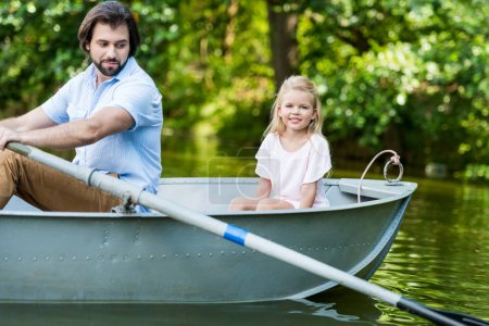side view of father and daughter riding boat on lake at park