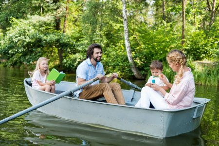 smiling young family riding boat on river at park