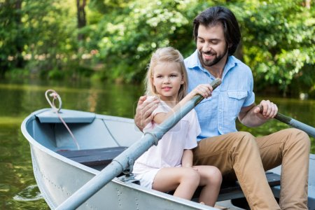 happy father and daughter riding boat and embracing on lake at park