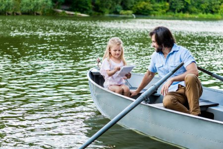 happy father and daughter with tablet riding boat on lake at park