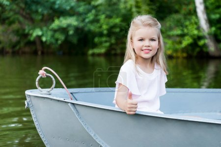 beautiful little child showing thumb up at camera while floating in boat on lake