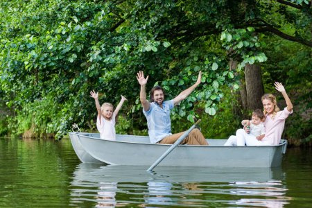 happy young family with raised hands riding boat on lake at park