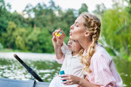 happy mother with son blowing soap bubbles while riding boat at park