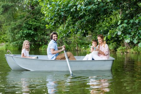 side view of smiling young family spending time together in boat on lake at park