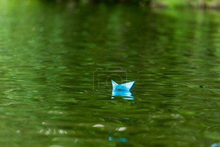 Photo pour Gros plan de bateau en origami papier bleue flottant à la surface de l'eau - image libre de droit