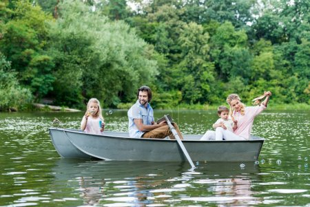 smiling young family spending time together in boat on lake at park