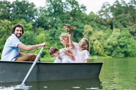 happy young family riding boat on lake at park together