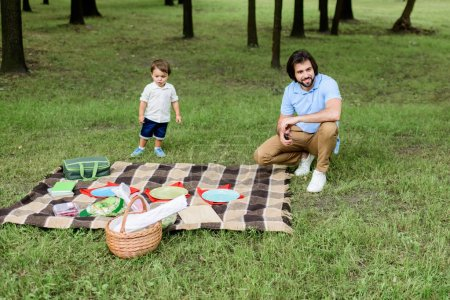handsome happy father with little son having picnic at park