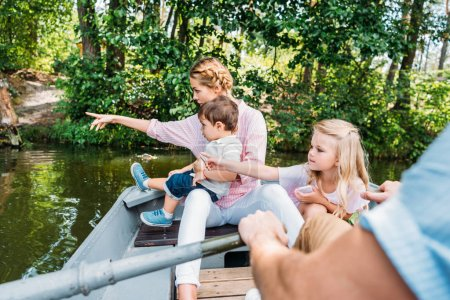 beautiful young family riding boat on lake and pointing somewhere at park
