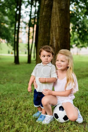 adorable little brother and sister with football ball embracing in park