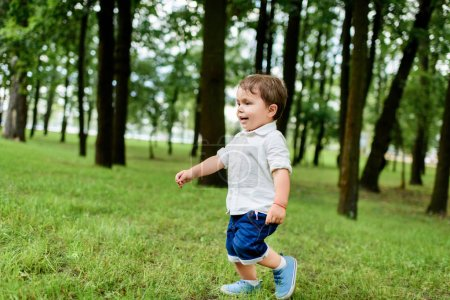 adorable little kid in white shirt and denim shorts running by park