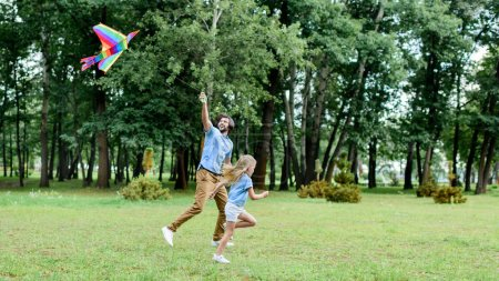 Photo for Side view of happy father and daughter running with kite at park - Royalty Free Image