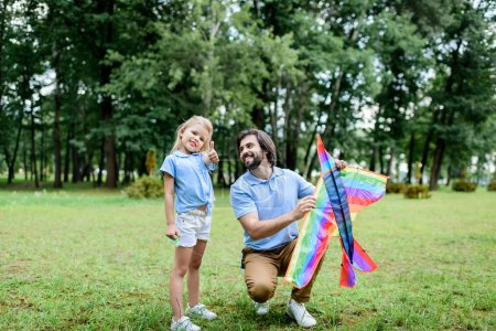handsome happy father with kite and adorable little daughter spending time together at park