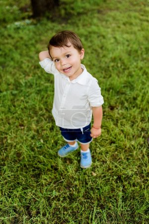 high angle view of adorable little kid standing on green grass and looking at camera