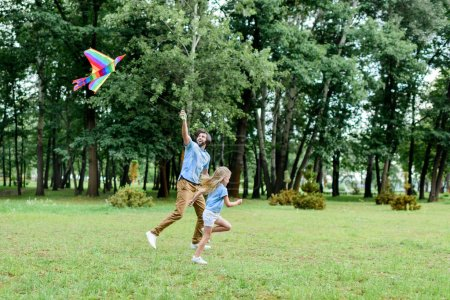 side view of handsome father and daughter running with kite at park