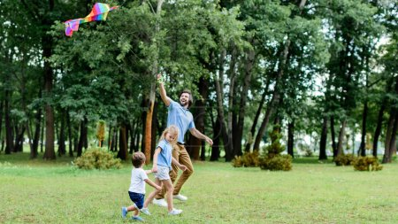 Photo for Side view of handsome father and kids playing with kite at park - Royalty Free Image