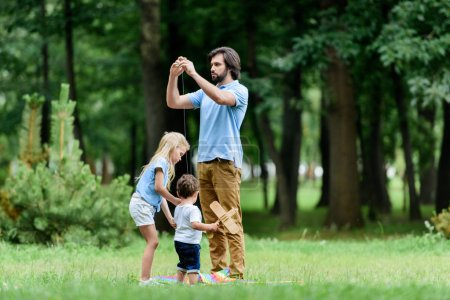 father and adorable little kids spending time together at park
