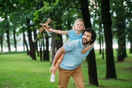 Photo for Smiling daughter piggybacking on happy father and playing with toy plane at park - Royalty Free Image