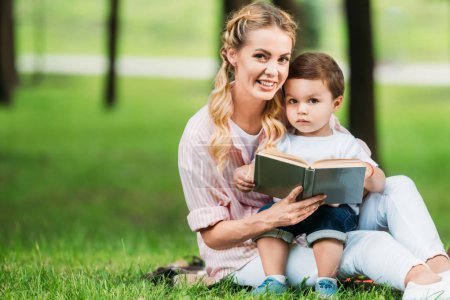 smiling mother and son sitting with book on grass at park and looking at camera