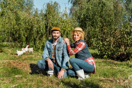 adult farmers sitting on grass and chickens running behind outdoors
