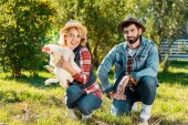couple of farmers in straw hats sitting on grass with chicken outdoors